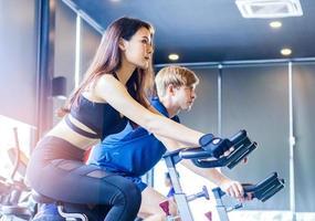 les jeunes couples font de l'exercice en faisant du vélo dans les concepts de gym exercice pour la santé de la nouvelle génération photo