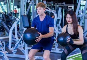 les jeunes femmes et hommes exercent dans le concept d'exercice sain de gym photo