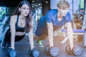 belle femme asiatique fait de l'exercice dans une salle de sport avec un entraîneur personnel concept de remise en forme bel homme pour la santé photo