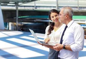 les hommes et les femmes d'affaires se tiennent debout et regardent les informations commerciales et commerciales avec leurs ordinateurs portables à l'extérieur dans le centre-ville moderne photo