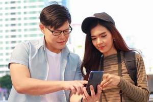 les jeunes touristes asiatiques utilisent des téléphones intelligents lors d'une visite en thaïlande concept de vivre un couple heureux photo