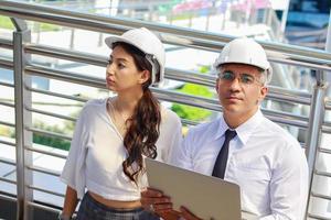 des ingénieurs hommes et femmes inspectent les projets de construction en plein air du site dans le centre-ville moderne les ingénieurs portent des casques de sécurité blancs pour la sécurité photo