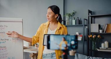 jeune enseignante asiatique conférence vidéo appelant sur smartphone parler par webcam apprendre enseigner dans le chat en ligne à la maison photo