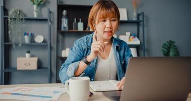 Une femme d'affaires asiatique utilisant un ordinateur portable parle à ses collègues du plan lors d'un appel vidéo tout en travaillant de la maison au salon photo