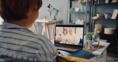 jeune fille asiatique utilisant un ordinateur portable réunion d'appel vidéo parler avec le père et la mère de la famille âgée tout en travaillant à domicile assis sur un canapé dans le salon photo