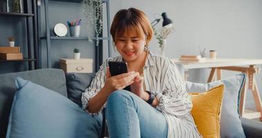 jeune femme asiatique utilisant un message texte sur smartphone ou consultez les médias sociaux sur un canapé dans le salon de la maison photo