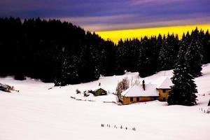 bâtiment jaune dans un paysage enneigé au coucher du soleil photo