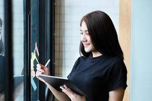 une employée de l'entreprise utilise une tablette et un bloc-notes pour analyser les budgets de l'entreprise photo