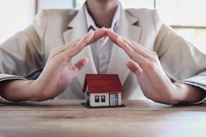 main de femme protégeant une maison sous les mains photo