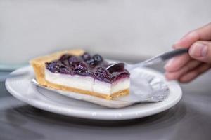 femme main tenant une cuillère mangeant un gâteau au fromage aux bleuets photo