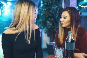 deux jolies femmes sont assises à la table du café et parlent photo