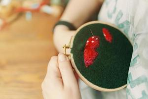 la fille brode le chapeau de champignon sur le tissu vert photo
