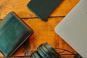vue de dessus des écouteurs smartphone et portefeuille en cuir sur table en bois photo