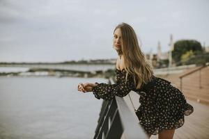 Jeune femme brune aux cheveux longs debout au bord de la rivière photo