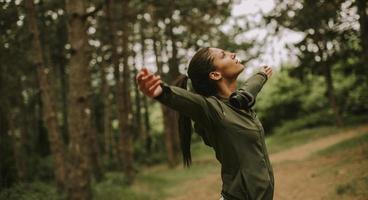 jeune femme avec des écouteurs preading ses bras dans la forêt parce qu'elle aime s'entraîner à l'extérieur photo