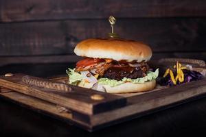 cheeseburger sur un plateau en bois dans un restaurant, sur fond sombre photo