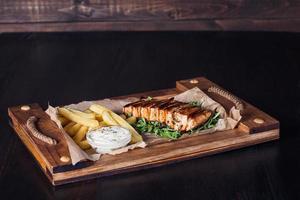 steak de filet de saumon avec frites sur un plateau en bois, belle portion, fond sombre photo
