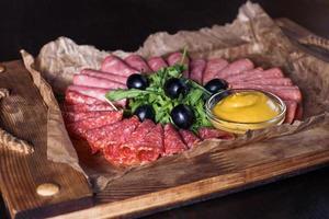 saucisse coupée aux herbes et sauce sur un plateau en bois, belle portion, fond sombre photo