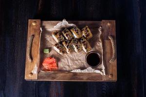 rouleaux de fruits de mer sur un plateau en bois, belle portion, fond sombre photo