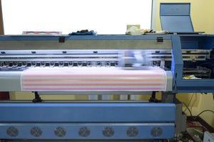 imprimante à jet d'encre grand format travaillant sur des feuilles d'autocollants photo