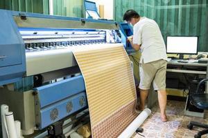 le technicien recharge la couleur de l'encre de l'imprimante à jet d'encre pendant l'impression de l'autocollant de la carte photo