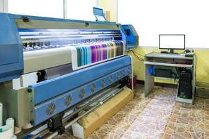 grande imprimante à jet d'encre fonctionnant en cmyk multicolore sur une bannière en vinyle avec contrôle par ordinateur photo