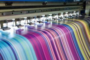 grande imprimante à jet d'encre fonctionnant en cmyk multicolore sur une bannière en vinyle photo