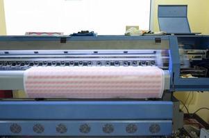 imprimante à jet d'encre grand format travaillant sur des feuilles d'autocollants avec une marque photo