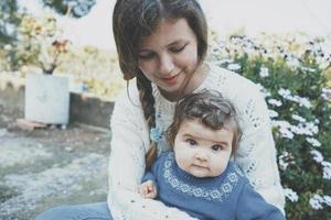 jeune maman étreignant son bébé et profitant d'une journée de printemps dans le jardin photo