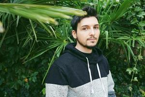 un jeune homme séduisant au calme debout et regardant la caméra avec des plantes d'extérieur derrière lui photo