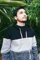 un jeune homme séduisant au calme debout et levant les plantes d'extérieur derrière lui photo