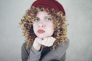 Portrait en gros plan d'une belle et jeune femme drôle ennuyée ou en colère aux yeux bleus et aux cheveux blonds bouclés portant un bonnet de laine rouge photo