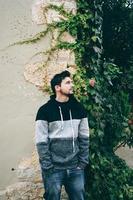 un jeune homme séduisant au calme debout avec des plantes d'extérieur derrière lui photo