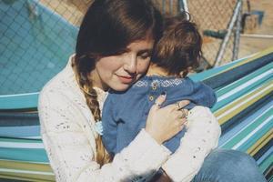 image sur la vraie maternité d'une jeune maman étreignant son bébé photo