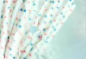 une belle macro colorée de bulles d'huile sur l'eau avec un flou de points rouges et bleus sur des pailles blanches en arrière-plan avec filtre vintage photo