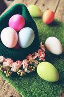 un beau gros plan coloré d'œufs de pâques dans un panier en laine avec des fleurs sur de l'herbe verte et un incroyable bokeh de tables en bois en arrière-plan photo