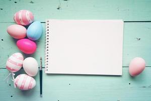 un beau gros plan coloré d'œufs de pâques isolés dans des couleurs unies et rayé à côté d'un ordinateur portable avec un espace sur une table en bois bleu pastel photo