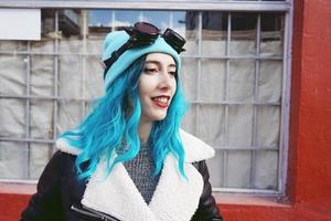 portrait d'une jeune femme punk ou gothique souriante aux cheveux bleus et portant des lunettes steampunk noires et une casquette en laine bleue dans une rue urbaine en plein air photo