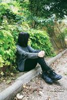 Belle femme brune caucasienne assise sur le sol dans un parc portant des vêtements punk ou gothiques et entourée de feuilles vertes photo