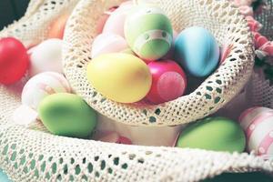 un beau gros plan coloré d'oeufs de pâques aux couleurs pastel unies et rayé dans un panier de fleurs photo