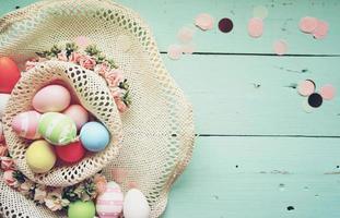 un beau gros plan coloré d'œufs de pâques aux couleurs pastel unies et rayé dans un panier avec des fleurs et de l'espace photo