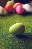 un beau gros plan coloré d'œufs de pâques verts sur l'herbe verte et un incroyable bokeh de nombreux œufs de différentes couleurs en arrière-plan photo