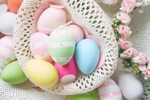 un beau gros plan coloré d'œufs de pâques aux couleurs unies et rayé dans un panier de fleurs photo