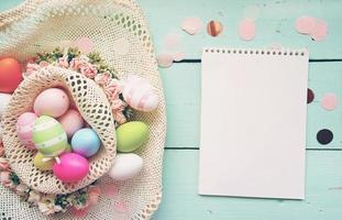 un beau gros plan coloré d'œufs de pâques aux couleurs pastel unies et rayé dans un panier de fleurs par un cahier avec un espace vide photo