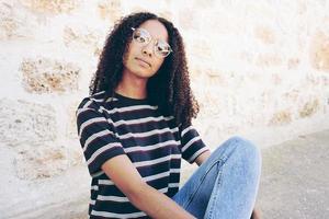 un portrait d'une jeune femme noire sérieuse portant des lunettes, un jean et un t-shirt rayé, assise sur le sol et les cheveux bouclés photo