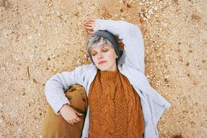 Une jeune femme de race blanche aventurière allongée sur un sol granuleux à côté d'un sac à dos portant un pull en laine et une casquette avec les yeux fermés et l'orange comme couleur principale photo