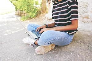 une jeune femme noire aux cheveux bouclés portant un jean et un t-shirt rayé, assise par terre et travaillant ou faisant ses devoirs photo