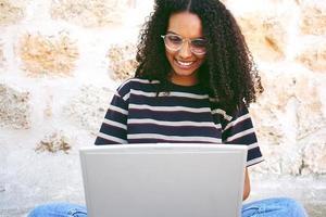 un portrait d'une jeune femme noire souriante et heureuse aux cheveux bouclés portant des lunettes, un jean et un t-shirt rayé, assise par terre et travaillant ou faisant ses devoirs photo