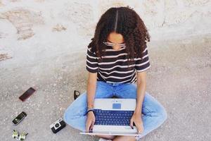 un portrait d'une jeune femme noire concentrée aux cheveux bouclés portant des lunettes, un jean et un t-shirt rayé, à côté de la technologie comme les smartphones et les appareils photo, assise par terre et travaillant ou faisant ses devoirs photo