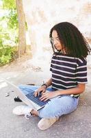 un portrait d'une jeune femme noire concentrée aux cheveux bouclés portant des lunettes, un jean et un t-shirt rayé, assise par terre et travaillant ou faisant ses devoirs photo